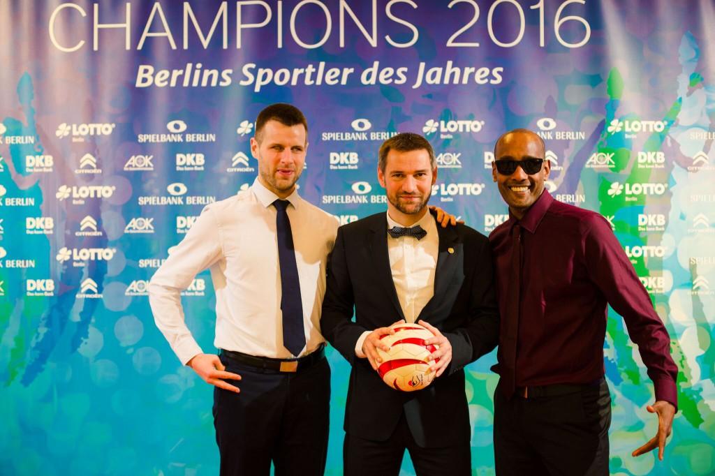 Alex, Enrico und Mulle stehen vor dem Werbebanner der Champions Gala